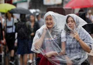 Young women arrive amid heavy rain for the opening of the 183rd Oktoberfest beer festival in Munich