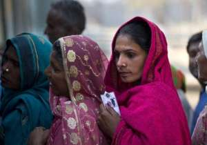 A women wait in a queue to cast their votes at a polling- India Tv