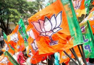 File pic - A BJP worker waves party flag during a...