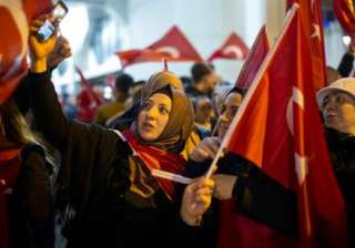 Demonstrators wave turkish flags outside the...