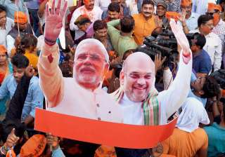 BJP workers carry a cut-out of PM Narendra Modi...