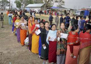 Voters stand in queues at a polling center to...
