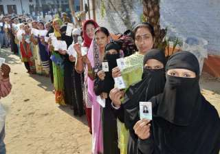 Women line up at a polling booth in Varanasi...