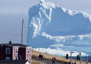 A 150-feet iceberg floats past Canadian village -...