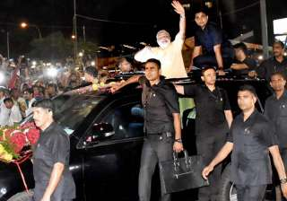 PM Modi waves at people during a road show in...