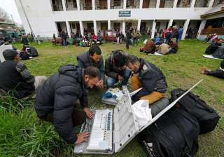 Polling staff checking EVMs before heading to...