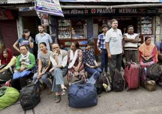 Stranded tourists wait at a bus stand in...