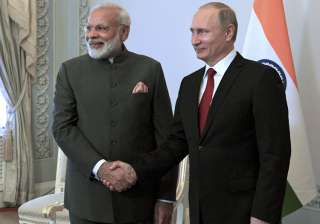 Putin shakes hands with Modi at the St....