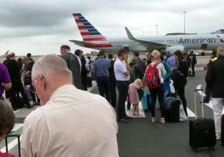 Passengers stand on the tarmac after being...