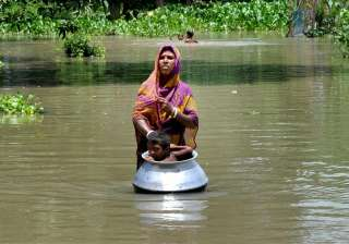 A woman with her child in flood affected...