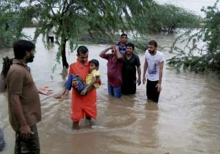 People wade through floodwaters after heavy...