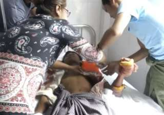 A man lying on a bed in a hospital in Buthidaung...