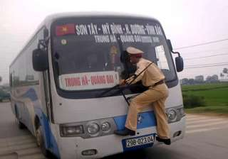 vietnamese traffic cop risks life to challan bus...
