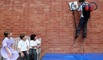 spider boy in uk scales walls with vacuum...