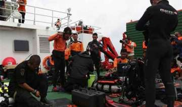 divers enter water in search of wreckage from...