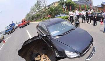 chinese driver has lucky escape as sinkhole...