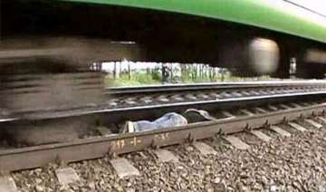 russian girl lies on tracks as train speeds over...
