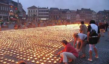 thousands help form giant candle star for charity...