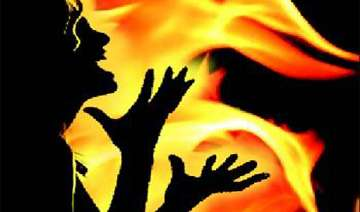 woman set ablaze by husband for opposing extra...