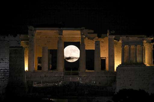 An extra large moon rose behind the Propylaia at the Acropolis hill in Athens.
