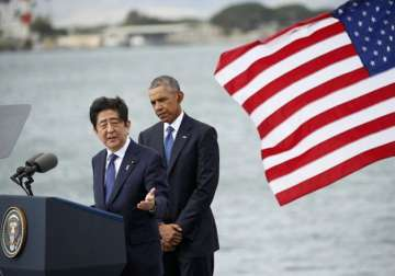 Shinzo Abe delivers remarks as Barack Obama looks...