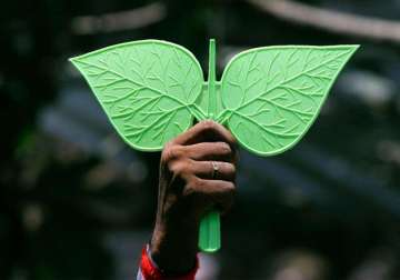 A man displays the election symbol of AIADMK -...