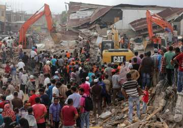 Rescuers search for victims under the rubble of...