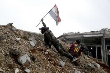 A Syrian army soldier places a Syrian national...
