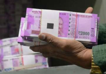 File pic - A bank official carrying new Rs 2,000...
