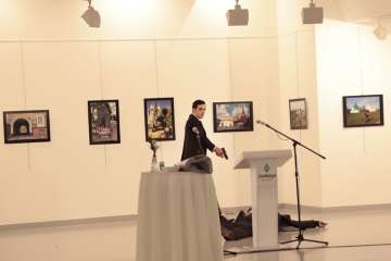 Gunman looks on after shooting Russian envoy to...