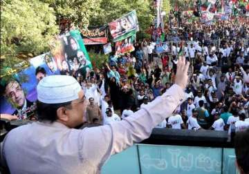 Zardari waves to supporters who gathered near...