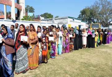 Women voters wait to cast their votes at a...