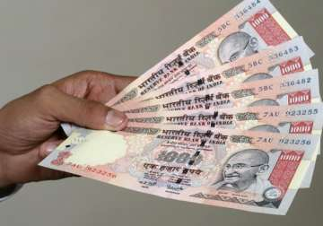 File pic - A man displays scrapped Rs 1,000 notes...