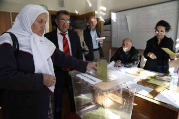 A woman casts a ballot inside a polling station...