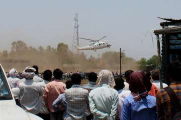 A crowd looks on as the helicopter with...