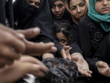 Mosul residents reach out for baked cookies at a...