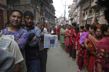 Nepalese stand in a queue to cast their votes...