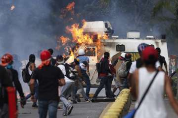 Anti-govt protesters set fire to an armored...