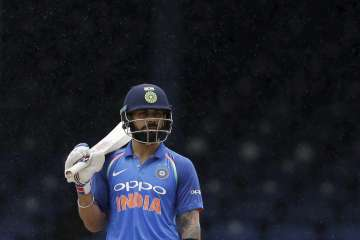 Virat Kohli reacts after rain stopped play at the...