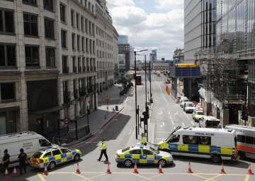Police vans block access to a street after an...