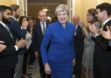 Britain's PM Theresa May applauded by staff as...