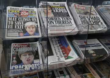 Newspapers fronted with photos of May are...