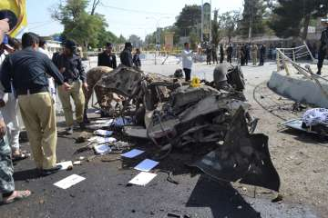 Pakistani police officers examine the site of an...