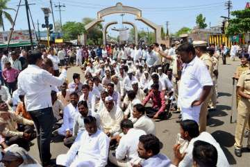Farmers block the road during a protest in...