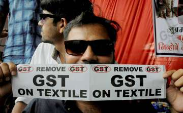 A textile trader with anti-GST poster during a...