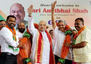 Amit Shah and Manohar Parrikar being garlanded at...