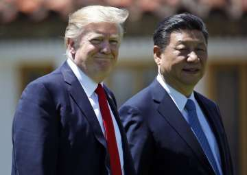 File pic - Trump and Jinping walk together after...