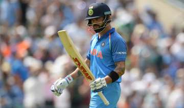 Virat Kohli of India leaves the field after being...
