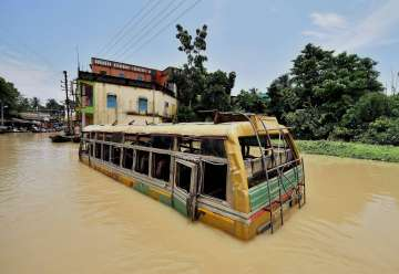 A bus submerged in flood waters at Ghatal in...