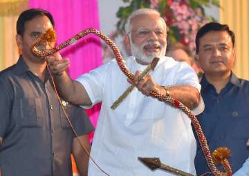 PM Modi holds a bows and arrow during Dussehra...
